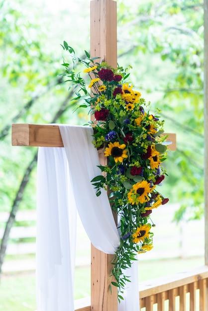 Colpo verticale del primo piano di un bouquet di fiori su una croce di legno ricoperta da un tessuto bianco Foto Gratuite
