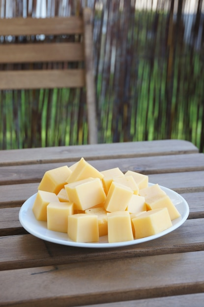 Colpo verticale del primo piano dei blocchi di formaggio gouda su un piatto bianco su una superficie di legno Foto Gratuite