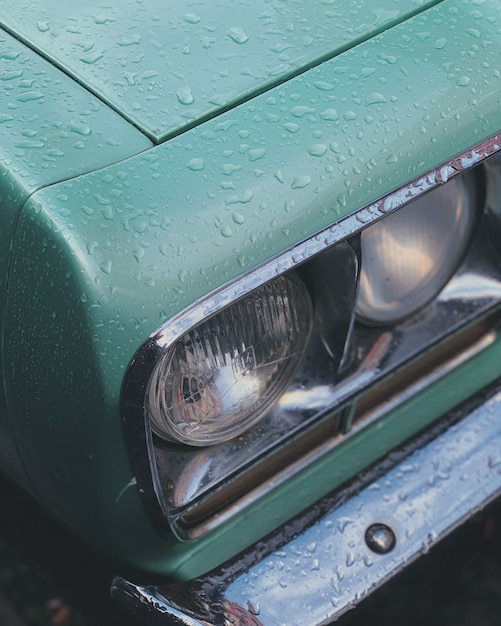Vertical closeup shot of a green car headlamps Free Photo