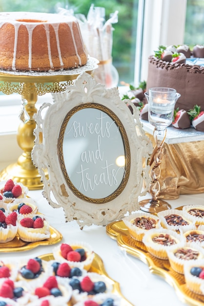フレームに「sweetsandtreats」と書かれたデザートテーブルの垂直クローズアップショット 無料写真