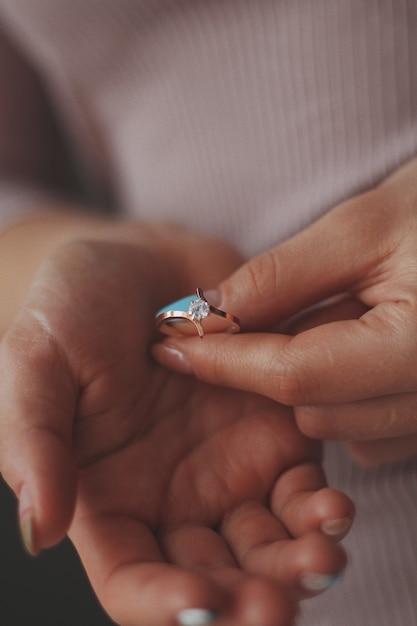美しいゴールドダイヤモンドリングを保持している女性の垂直のクローズアップショット 無料写真