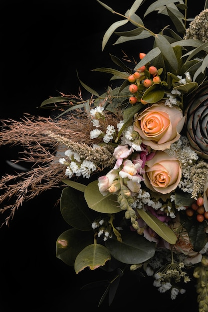 黒の背景にオレンジと茶色のバラの豪華な花束の垂直クローズアップショット 無料写真
