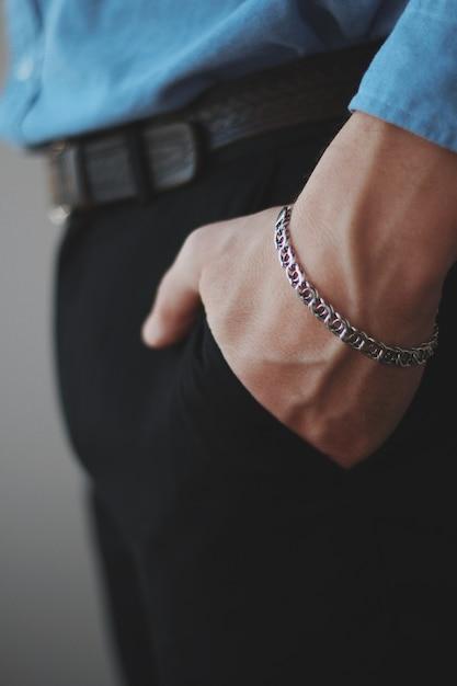 주머니에 그의 손으로 은색 팔찌를 착용하는 남성의 수직 근접 촬영 샷 무료 사진