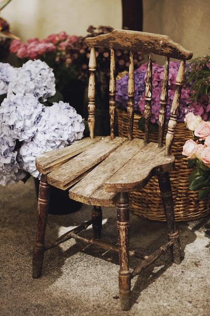花のバスケットに囲まれたヴィンテージの木製の椅子の垂直クローズアップショット 無料写真