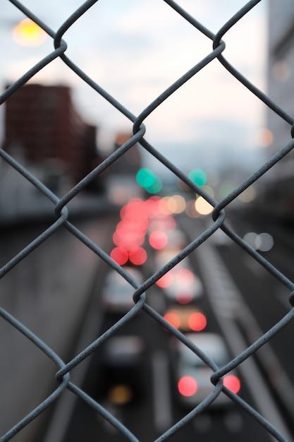 通りのぼやけた背景に灰色のチェーンリンクフェンスの垂直のクローズアップショット 無料写真