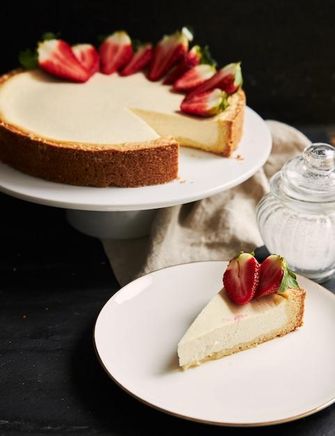 白いプレート上のイチゴのチーズケーキの垂直クローズアップショット 無料写真