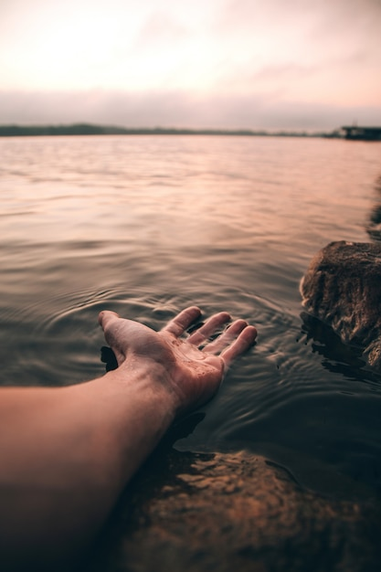 Vertical closeup shot of a person with his hand in water Free Photo