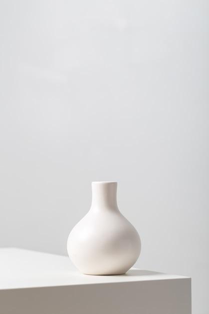 Primo piano verticale di un vaso di argilla bianca sul tavolo sotto le luci su uno sfondo bianco Foto Gratuite