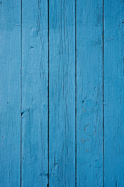 Primo piano verticale di una parete in legno dipinta di blu sotto le luci Foto Gratuite