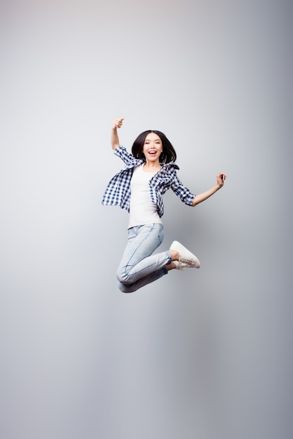 Вертикальный портрет в полный рост сумасшедшей женщины, прыгающей Premium Фотографии