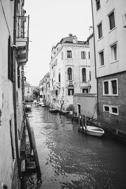 イタリア、ベニスのボートと古代の建物のある水路の垂直グレースケール画像 無料写真