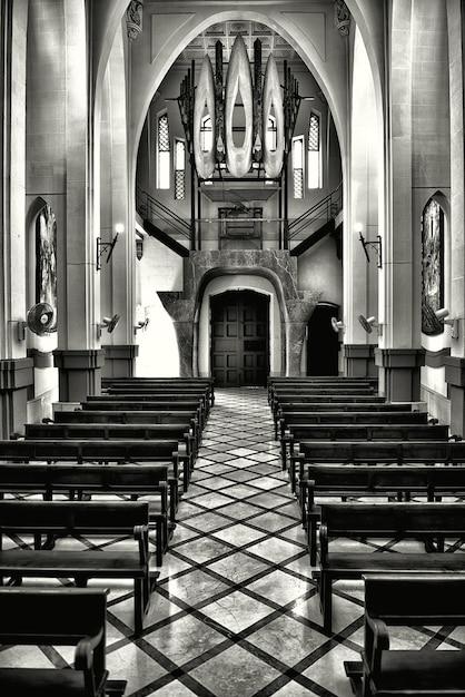 Colpo verticale in scala di grigi dell'interno di una vecchia chiesa cristiana storica Foto Gratuite