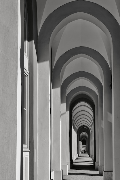 Vertical grayscale shot of a long corridor with multiple arch-shaped columns Free Photo
