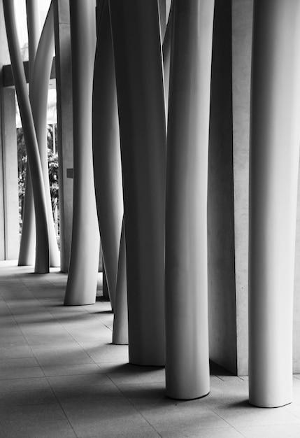 구부러진 기둥이있는 현대적인 건물 내부의 수직 회색조 샷 무료 사진