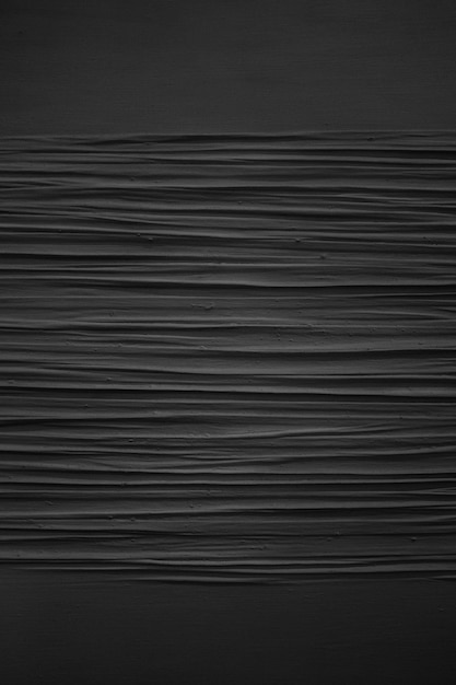Vertical grey scale shot of the patterns on a black painted wall Free Photo