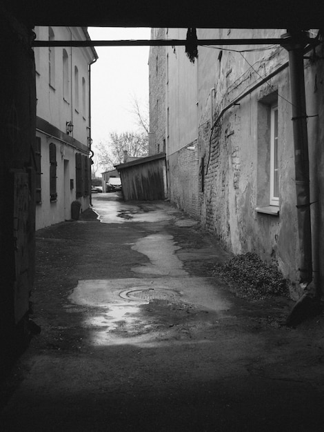Vertical grey-scale shot of a street with old buildings and rainwater in the ground Free Photo