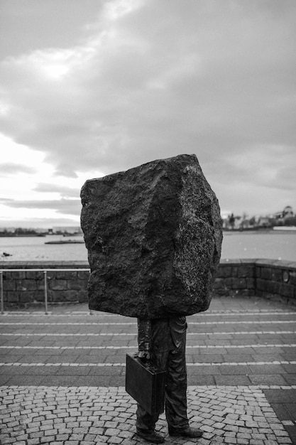 Vertical greyscale conceptual shot of a rock-headed person carrying a bag -concept of dept Free Photo