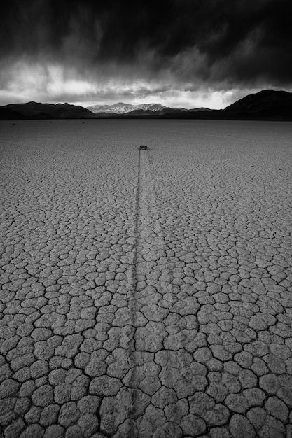 Vertical greyscale shot of a deserted ground of sand surrounded by a mountainous scenery Free Photo