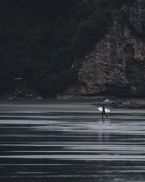 垂直のグレースケールショットoサーフィンデスクで水に入る人 無料写真