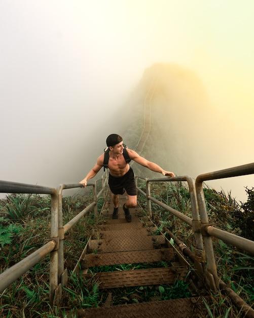 Colpo verticale di alto angolo di un maschio che sale le scale su una collina - superando il concetto di sfide Foto Gratuite