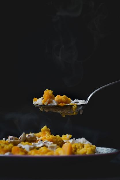 米、鶏肉、イエローソースが入ったおいしい温かい料理の垂直ハイアングルショット 無料写真