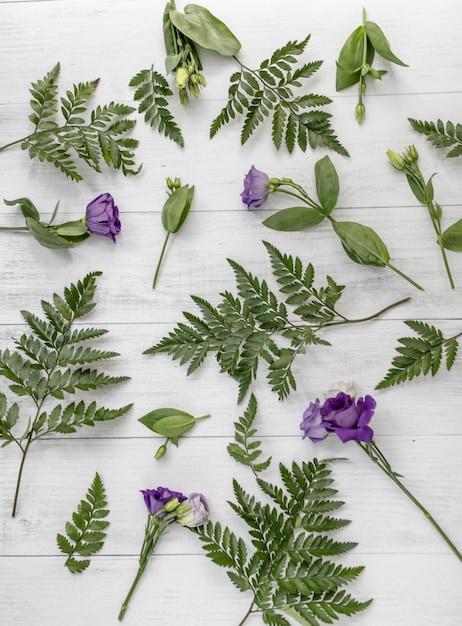 Colpo verticale ad alto angolo di fiori viola lisianthus e foglie verdi su una superficie di legno Foto Gratuite