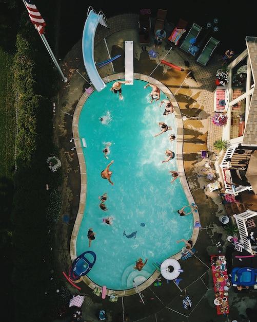 米国の日光の下でのパーティー中のプールの垂直高角度ビュー 無料写真