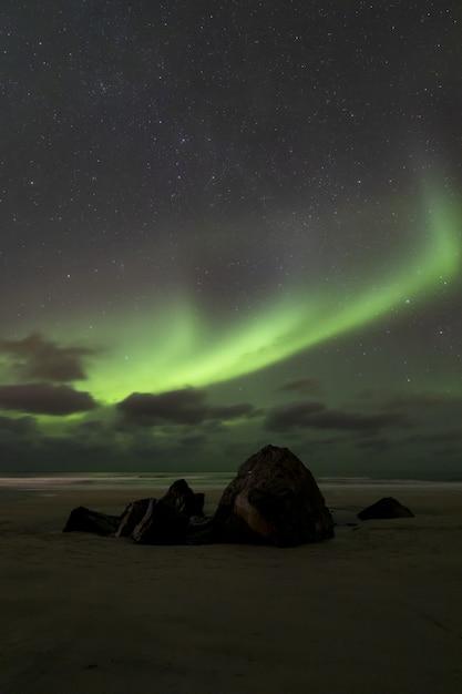 별이 빛나는 하늘을 배경으로 대서양의 숨막히는 오로라 현상의 수직 이미지 무료 사진