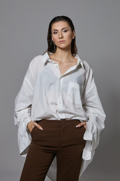 검은 머리를 가진 유행 자신감 젊은 유럽 여성의 수직 이미지는 다시 포즈를 취하고 우아한 갈색 바지와 특대 흰색 셔츠를 입고 주머니에 손을 유지 무료 사진