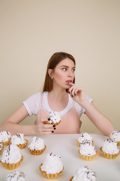ケーキとテーブルで物思いにふける女性の垂直方向の画像 無料写真