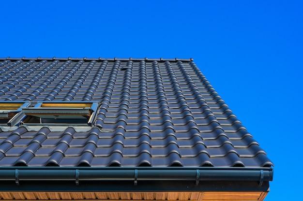 건물의 검은 지붕의 수직 낮은 각도 근접 촬영 샷 무료 사진