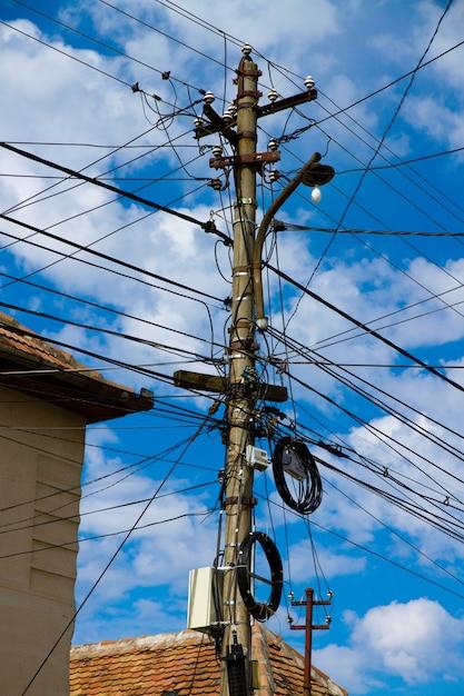 Inquadratura dal basso verticale di molti cavi elettrici sotto un cielo nuvoloso Foto Gratuite