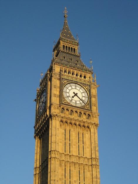 Вертикальный снимок биг-бена в лондоне под голубым небом под низким углом Бесплатные Фотографии