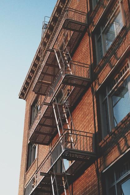 Colpo verticale di un vecchio edificio in mattoni con la scala di uscita di emergenza sul lato Foto Gratuite