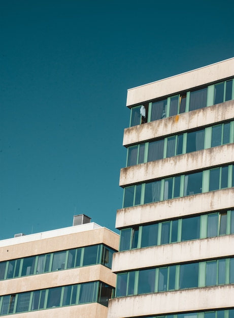 Vertical low angle shot of an old building with broken windows under the blue sky Free Photo