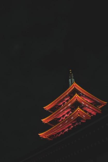 Colpo verticale di angolo basso del tempio di senso-ji a tokyo, giappone durante la notte Foto Gratuite