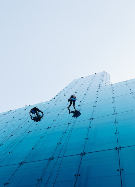 Inquadratura dal basso verticale di due persone che si arrampicano su un alto edificio di vetro durante il giorno Foto Gratuite