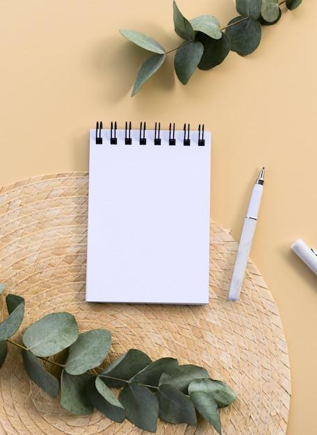 Вертикальный минимальный макет блокнота. спиральный блокнот с копией пространства и листьями эвкалипта. Premium Фотографии