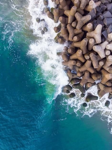 바위에 물결 모양의 푸른 바다의 수직 오버 헤드 공중 샷 무료 사진