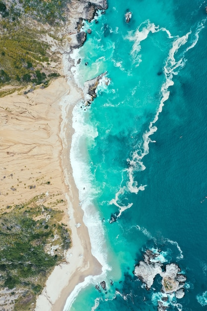 Vertical overhead shot of the beautiful shoreline of the sea with blue clean water and sandy beach Free Photo
