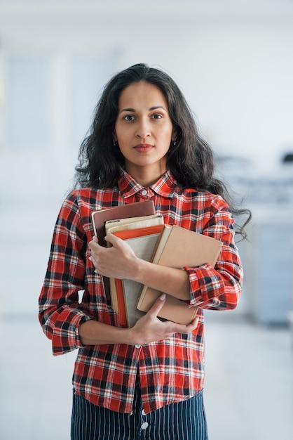 Foto verticale di attraente giovane donna in piedi in ufficio e tenendo libri e documenti Foto Gratuite