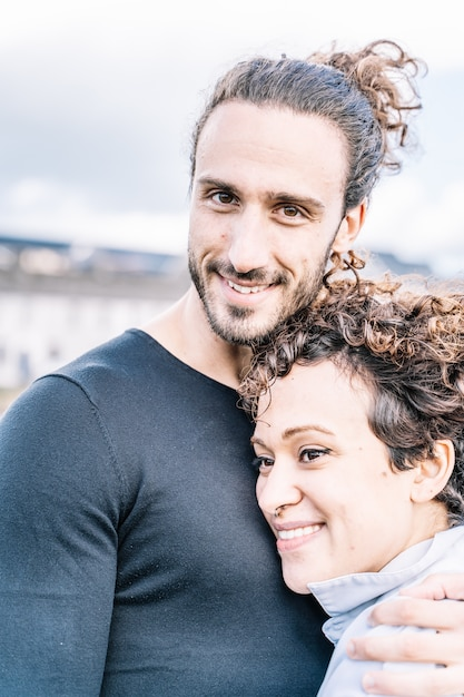 Vertical photo of a couple embraced by the shoulder with the sea out of focus Free Photo