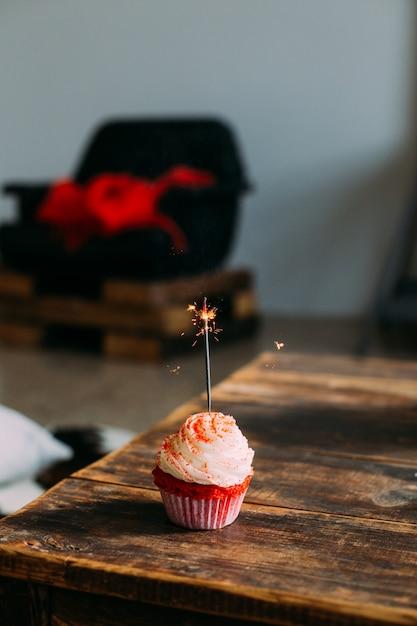線香花火キャンドル、フロスティングと砂糖で飾られた赤いベルベットピンクのカップケーキのスマートフォンのスクリーンセーバーの垂直写真 無料写真