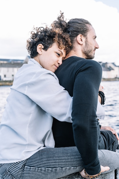 Vertical photo of a girl hugging her partner  back with the  sea out of focus Free Photo