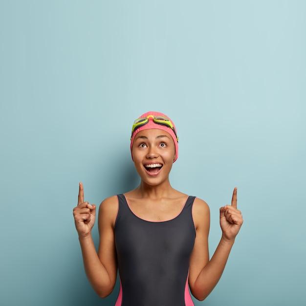 水着を着て、楽しい趣味と夏のアクティブな休息を楽しんでいる楽しい暗い肌の女性の垂直写真 無料写真