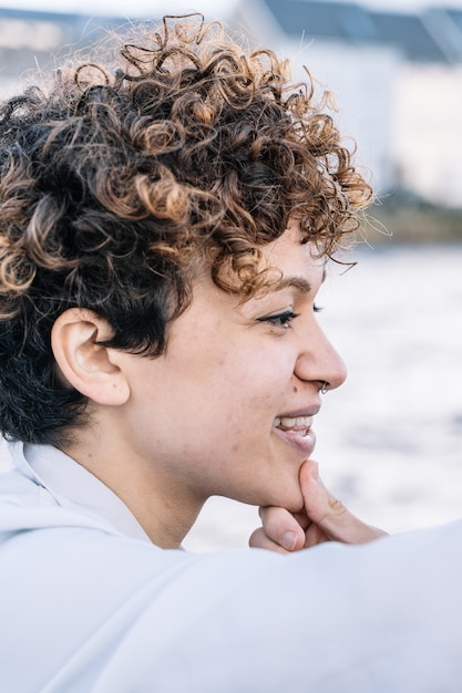 Vertical photo of a young girl's face with curly hair while her chin is stroked Free Photo
