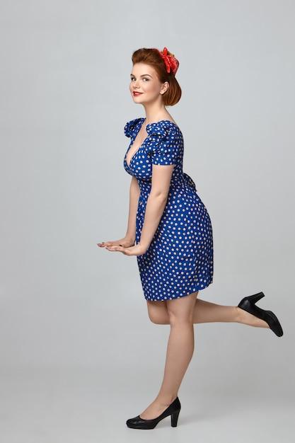 Immagine verticale di una splendida giovane donna dai capelli rossi che indossa scarpe nere col tacco alto e vestito blu punteggiato con collo basso tagliato in posa, tenendosi per mano davanti a lei e tenendo la gamba sollevata Foto Gratuite