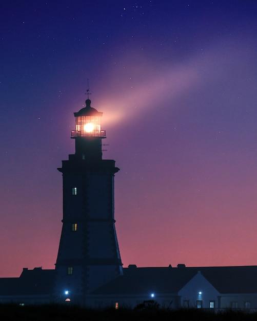Immagine verticale di un faro sotto un cielo stellato la sera Foto Gratuite
