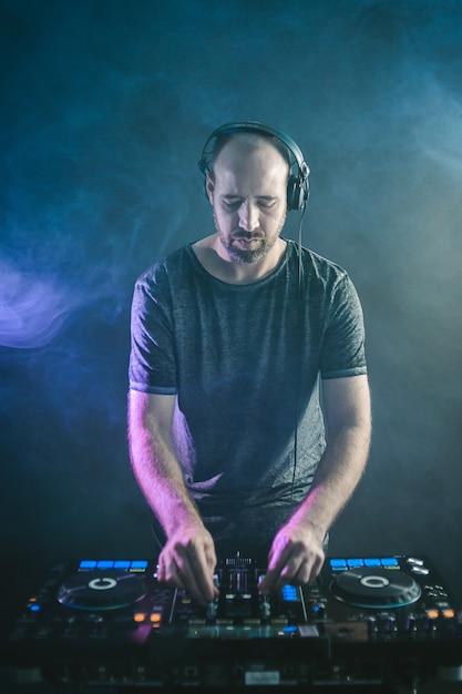 Immagine verticale di un dj maschio sotto le luci blu e il fumo Foto Gratuite