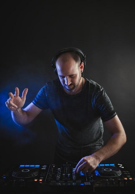 Immagine verticale di un dj maschio che lavora sotto le luci blu in uno studio Foto Gratuite